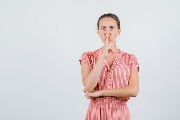 Jeune femme en robe rayée montrant le geste de silence et à la stricte vue de face.
