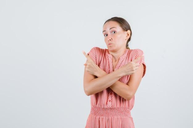 Jeune femme en robe rayée pointant vers le côté et à la perplexité, vue de face.