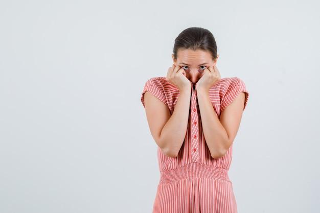 Jeune femme en robe rayée se cachant le visage derrière le col et à la peur, vue de face.