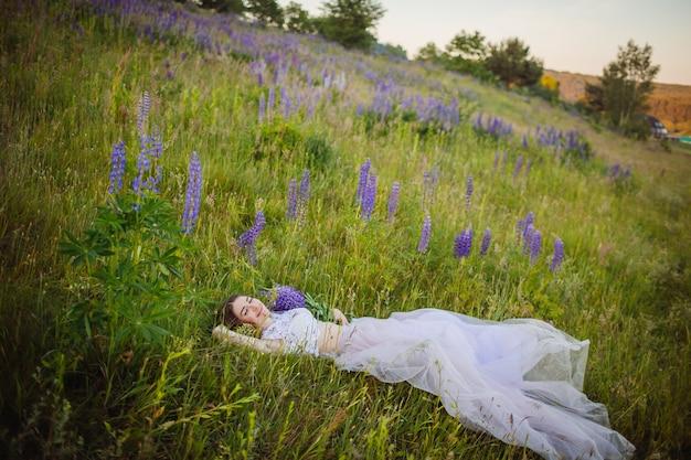 Jeune femme en robe riche se trouve avec bouquet de fleurs violettes sur champ vert