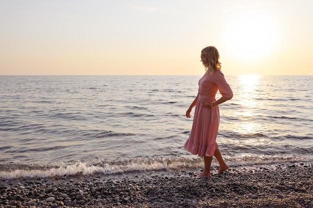 Jeune femme en robe rose marche lentement le long de la côte de surf pieds nus et regarde l'horizon