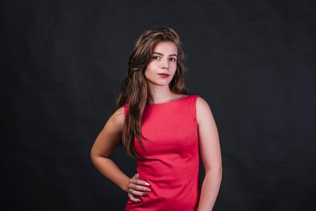 Jeune femme en robe rose, regardant la caméra