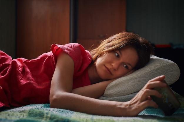 Jeune femme en robe rouge allongée sur le lit et regarder la vidéo sur smartphone