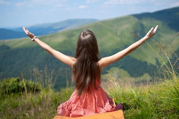 Jeune femme en robe rouge assise sur une prairie herbeuse un jour venteux dans les montagnes d'été en levant les mains en profitant de la vue sur la nature.