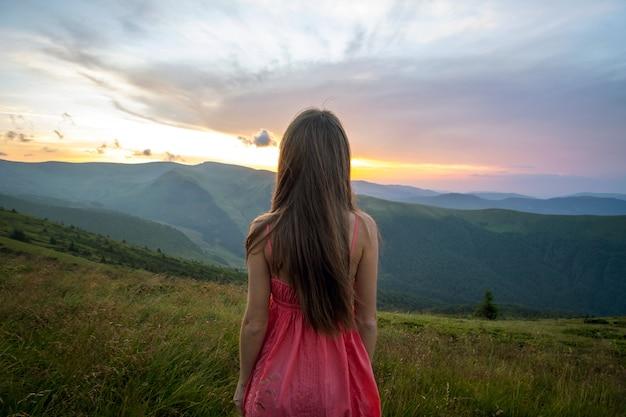 Jeune femme en robe rouge debout sur terrain herbeux dans les montagnes, profitant de la vue sur la nature.