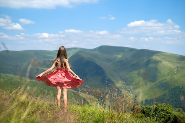 Jeune femme en robe rouge debout sur un terrain herbeux par une journée venteuse dans les montagnes d'été, profitant de la vue sur la nature.