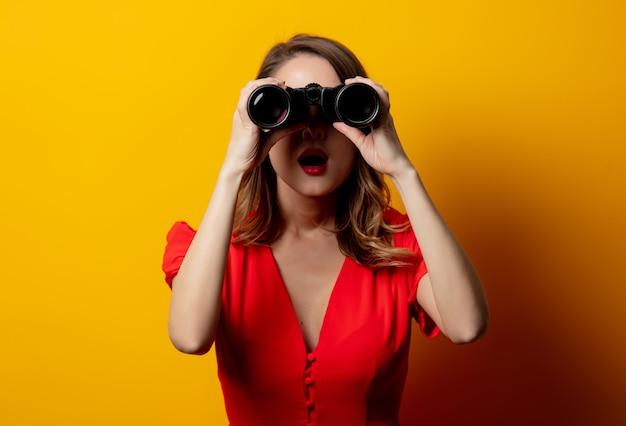 Jeune femme en robe rouge avec des jumelles sur le mur jaune
