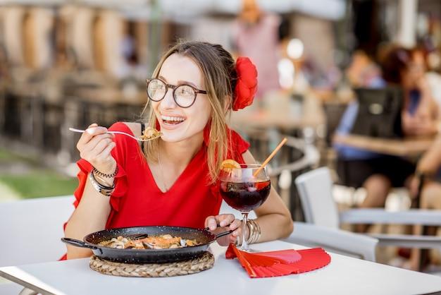 Jeune femme en robe rouge mangeant de la mer paella, plat de riz traditionnel valencien, assis à l'extérieur au restaurant à valence, espagne