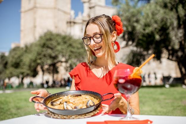 Jeune femme en robe rouge avec paella de mer, plat de riz traditionnel valencien, assise à l'extérieur au restaurant du centre de la vieille ville de valence