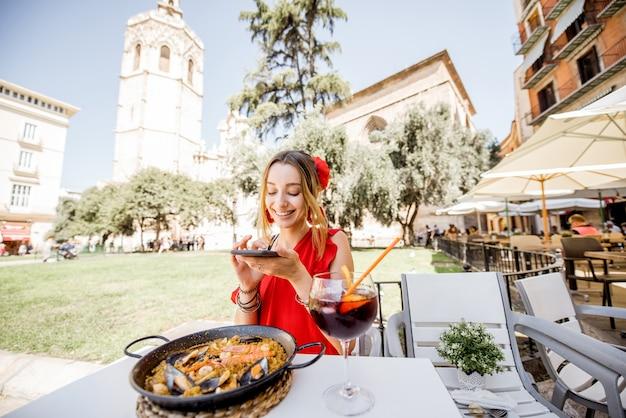 Jeune femme en robe rouge photographiant la mer paella, plat de riz traditionnel valencien, assise à l'extérieur au restaurant à valence