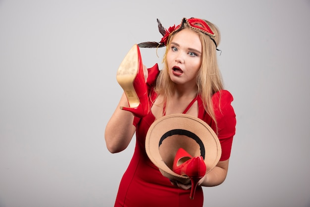 Jeune femme en robe rouge regardant les talons.