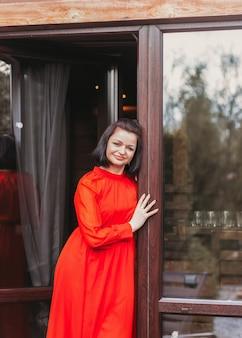 Une jeune femme en robe rouge se tient près d'une grande fenêtre et pense à quelque chose