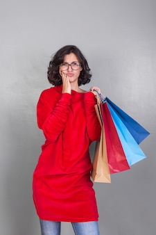 Jeune femme en robe avec des sacs à provisions