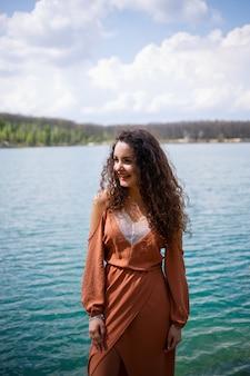 Une jeune femme en robe se dresse sur une maçonnerie en bois au milieu d'un lac bleu. fille heureuse sourit et le soleil brille, jour d'été. elle a les cheveux longs bouclés et une apparence européenne