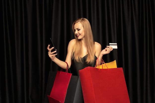 Jeune femme en robe shopping sur mur noir