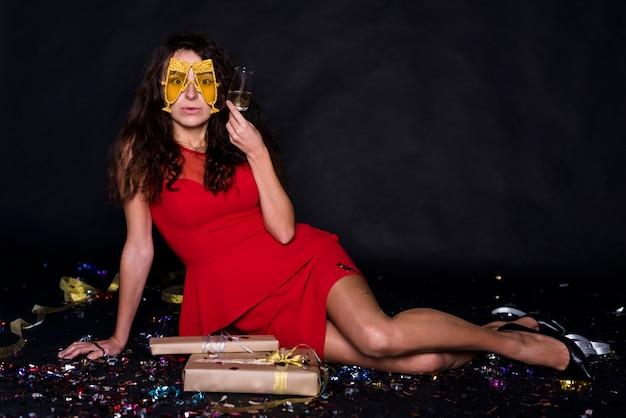 Jeune femme en robe de soirée avec verre et masque drôle près des boîtes à cadeaux