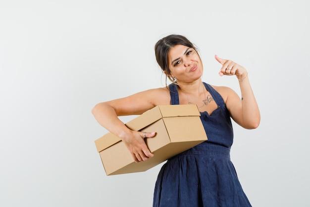 Jeune femme en robe tenant une boîte en carton, pointant vers l'avant et semblant joyeuse