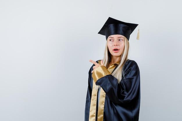 Jeune femme en robe universitaire pointant vers le côté gauche et à la surprise