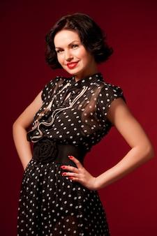 Jeune femme en robe vintage noire debout sur fond rouge