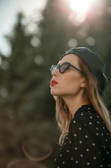Jeune femme en robe vintage noire à pois posant à l'extérieur