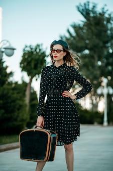 Jeune femme en robe vintage noire à pois avec valise rétro à la main, posant à l'extérieur