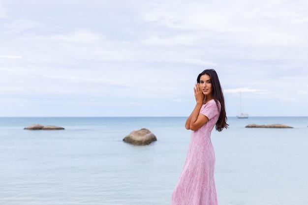 Jeune femme romantique aux longs cheveux noirs dans une robe sur la plage en souriant et en riant s'amuser seul