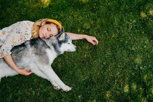 Une jeune femme romantique couchée avec un chien sur l'herbe