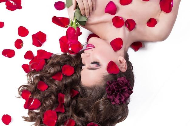 Jeune femme à la rose allongée parmi les pétales de rose. mode de vie et soins du corps