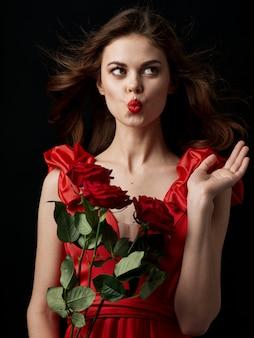 Jeune femme avec des roses rouges dans ses mains dans une robe rouge