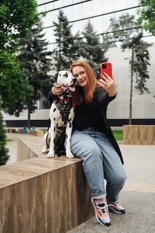 Jeune femme rougeâtre dans la rue avec son chien dalmatien prenant une photo avec un téléphone portable