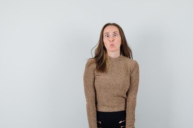 Jeune femme roulant les yeux en pull doré et pantalon noir et à amusé