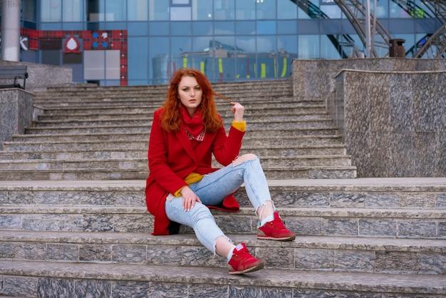 Une jeune femme rousse adulte dans une veste rouge, un jean bleu et des baskets rouges est assise sur les marches de...