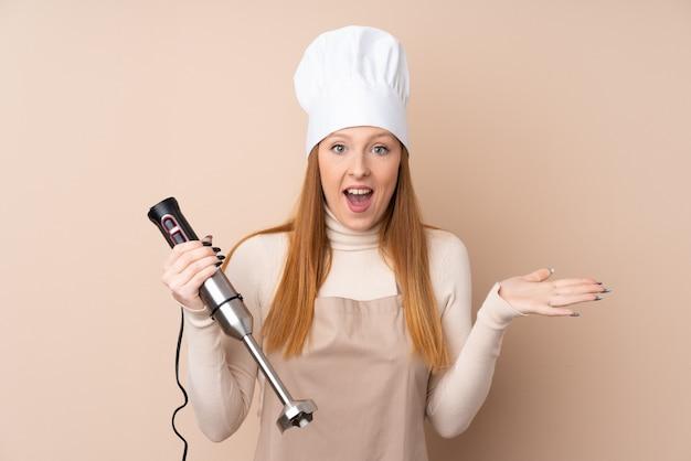 Jeune femme rousse à l'aide d'un mélangeur à main avec une expression faciale choquée