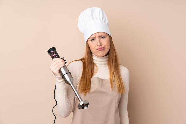 Jeune femme rousse à l'aide d'un mélangeur à main avec une expression triste