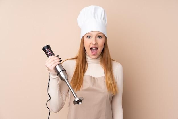 Jeune femme rousse à l'aide d'un mélangeur à main avec surprise et expression faciale choquée
