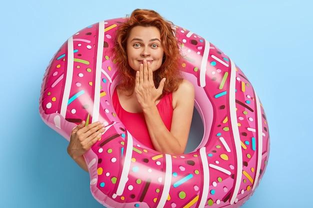 Une jeune femme rousse à l'air agréable rit joyeusement, garde la main sur la bouche, satisfaite de la vue imprenable sur la mer, vêtue d'un bikini rouge, porte un grand anneau de bain en caoutchouc, se repose l'été