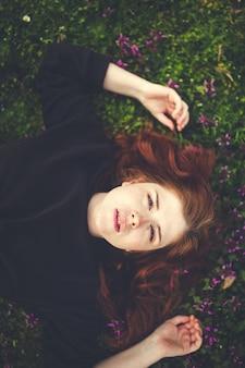 Jeune femme rousse allongée sur l'herbe touchant les fleurs