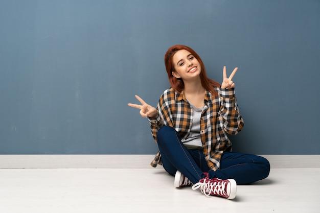 Jeune femme rousse assise sur le sol en souriant et en montrant le signe de la victoire à deux mains