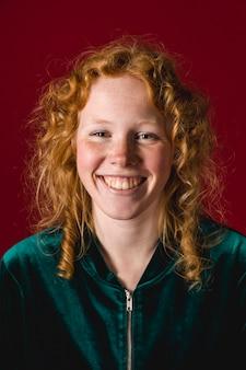 Jeune femme rousse attrayante, souriant à la caméra