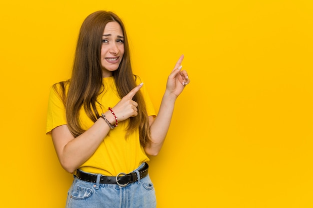 Jeune femme rousse au gingembre choqué pointant avec des index vers un espace de copie.
