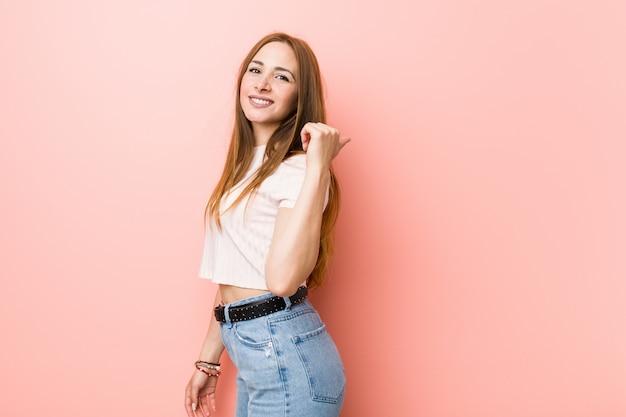 Jeune femme rousse au gingembre contre un mur rose pointe avec le doigt du pouce loin, riant et insouciant.
