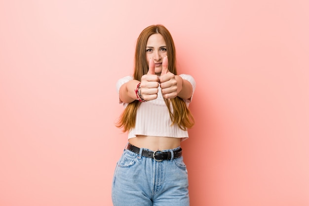 Jeune femme rousse au gingembre contre un mur rose avec le pouce levé, acclamations à propos de quelque chose, concept de soutien et de respect.