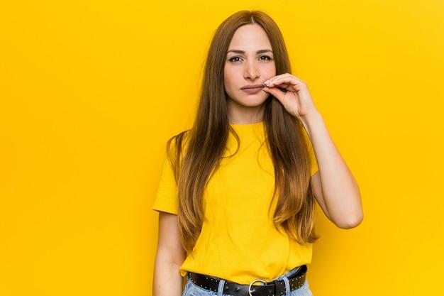 Jeune femme rousse au gingembre avec les doigts sur les lèvres en gardant un secret.