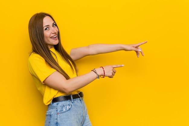 Jeune femme rousse au gingembre excité, pointant du doigt avec les index.