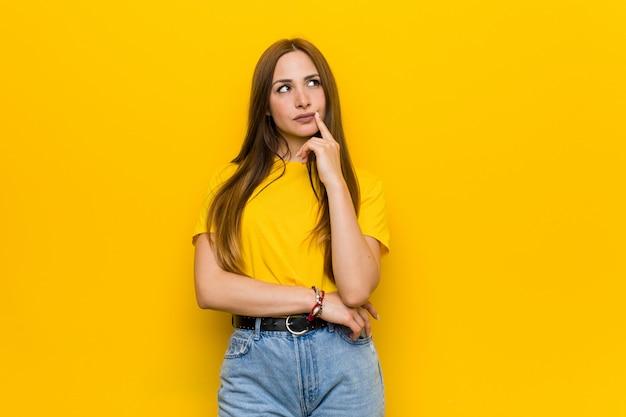 Jeune femme rousse au gingembre, regardant de côté avec une expression douteuse et sceptique