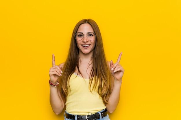 Jeune femme rousse au gingembre avec sans tache indique avec les deux doigts devant montrant un espace vide.