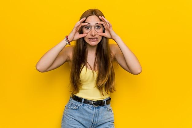 Jeune femme rousse au gingembre avec des taches de rousseur gardant les yeux ouverts pour trouver une occasion de réussir
