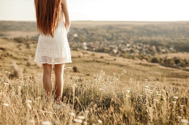 Jeune femme rousse aux cheveux longs en robe d'été blanche