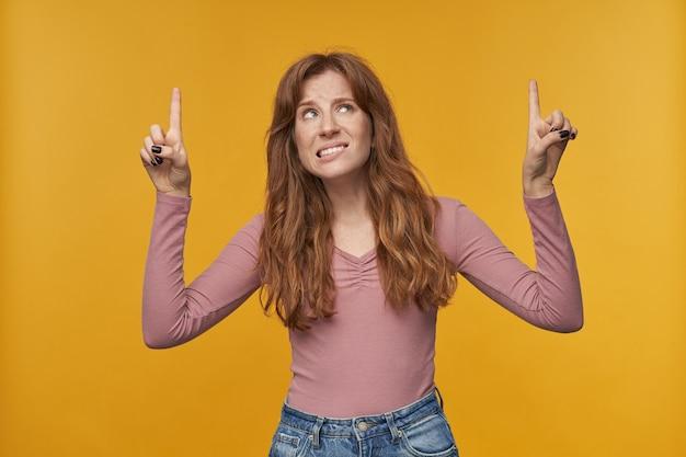 Jeune femme rousse aux cheveux ondulés et aux taches de rousseur, pointant le doigt vers le haut, se mordant la lèvre avec une expression faciale négative sur jaune