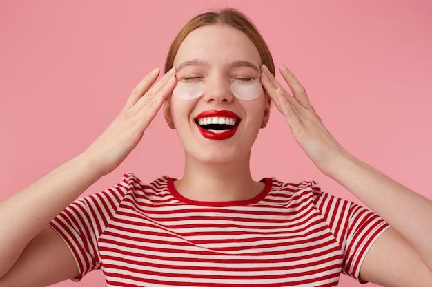 Jeune femme rousse aux lèvres rouges porte un t-shirt rayé rouge, avec des taches sous les yeux, masse les tempes, profite de temps libre pour prendre soin de soi, souriant largement. des stands.